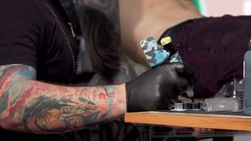 Tatoegeringskunstenaar die tatoegeringsmachine nemen, die bij zijn studio werken stock videobeelden