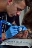 Tatoegeringskunstenaar in het werk Stock Afbeeldingen