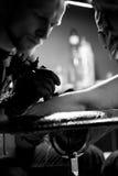 Tatoegeringskunstenaar wat tatoegering maken De hoofdwerken aangaande professionele machine en in steriele zwarte handschoenen Stock Foto