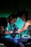 Tatoegeringskunstenaar wat tatoegering maken De hoofdwerken aangaande professionele machine en in steriele zwarte handschoenen Royalty-vrije Stock Afbeeldingen