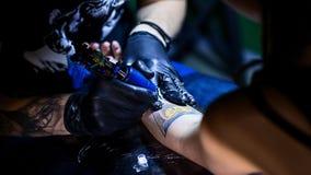 Tatoegeringskunstenaar wat tatoegering maken De hoofdwerken aangaande professionele machine en in steriele zwarte handschoenen Royalty-vrije Stock Fotografie