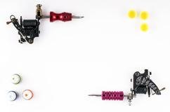 Tatoegeringsmachines met drie flessen van inkt en drie inktcontainers op witte achtergrond Royalty-vrije Stock Afbeeldingen