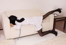 Tatortnachahmung. Krankenschwester auf dem Sofa Stockfotografie