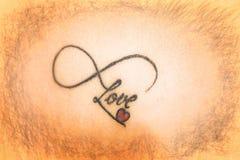 Tatouage abstrait sur la peau qui indique l'amour avec le coeur rouge smal Photographie stock