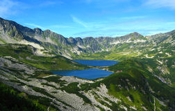 Tatra mountains in Poland, green hill, lake and rocky peak in the sunny day with clear blue sky Royalty Free Stock Photos