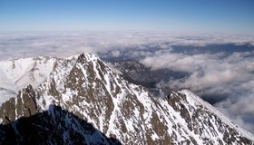 Tatra mountains in winter. High angle or aerial view of snow capped High Tatra mountains in winter above cloudscape, Slovakia royalty free stock image