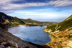 Tatry mountains in Poland - the pond called Czarny Staw with beautiful water color. Tatry mountains natural pond reflecting the sky and the mountains. The name stock photography