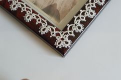 Closeup Corner detail Fine Thread Tatted Edging Picture Frame. With chains and rings and picots glued to a red Picture Frame royalty free stock photography