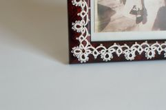 Corner detail Fine Thread Tatted Edging Picture Frame. Corner detail of Fine Thread Tatted Edging with chains and rings and picots glued to a red Picture Frame royalty free stock photo