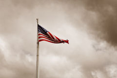 Tattered American Flag. Flying in Stormy Sky Stock Photos