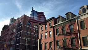 American Flag Flying by Apartment Buildings in New York`s Little Italy Neighborhood. A tattered American flag flaps in the wind in front of apartment buildings stock footage