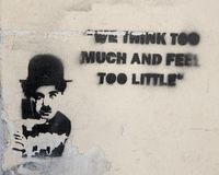 Tattered graffiti with image Charlie Chaplin and part of one of his famous quotes, `We think too much and feel too little`. Pictured is Graffiti with an image royalty free stock image