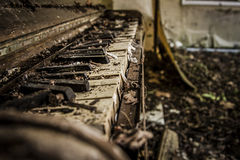 Tattered old abandoned piano. With broken keys royalty free stock photos