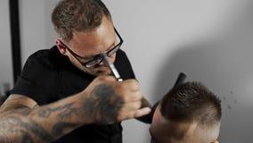 Tattoed理发师做顾客的理发在理发店通过使用剪刀和梳子,人` s理发和刮在 股票录像