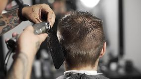 Tattoed barber makes haircut for customer at the barber shop by using hairclipper, man`s haircut and shaving at the stock footage