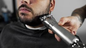 Tattoed barber shears the customer`s beard by using trimmer at the barber shop, man`s haircut and shaving at the. Hairdresser, barber at the shaving salon stock footage