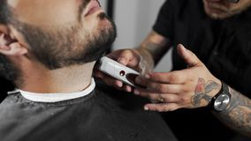 Tattoed barber shears the customer`s beard by using trimmer at the barber shop, man`s haircut and shaving at the. Hairdresser, shaving salon stock video