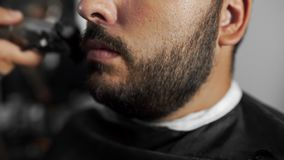 Tattoed barber shears the customer`s beard by using trimmer at the barber shop, man`s haircut and shaving at the. Hairdresser, barber shop stock video footage