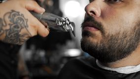 Tattoed barber shears the customer`s beard by using trimmer at the barber shop, man`s haircut and shaving at the stock video footage