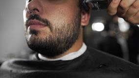 Tattoed barber shears the customer`s beard by using trimmer at the barber shop, man`s haircut and shaving at the. Hairdresser, shaving salon stock video footage