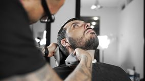 Tattoed barber shears the customer`s beard by using trimmer at the barber shop, man`s haircut and shaving at the. Hairdresser, shaving salon stock footage