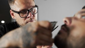 Tattoed barber shears the customer`s mustage by using trimmer and comb at the barber shop, man`s haircut and shaving at. The hairdresser, shaving salon stock footage