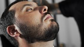 Tattoed barber shears the customer`s mustage by using trimmer and comb at the barber shop, man`s haircut and shaving at. The hairdresser, shaving salon stock video