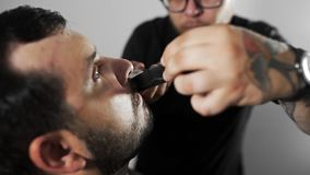 Tattoed barber shears the customer`s mustage by using trimmer and comb at the barber shop, man`s haircut and shaving at. The hairdresser, shaving salon stock video footage