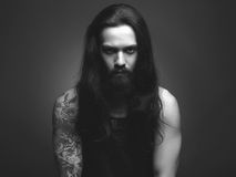 Tattoed bearded man in dark. Handsome bearded man.black and white portrait of Brutal hipster boy with tattoo Stock Photo