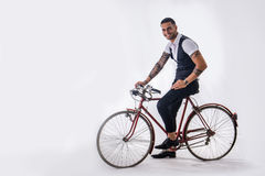 Tattoed elegant man cycling on bicycle Royalty Free Stock Image