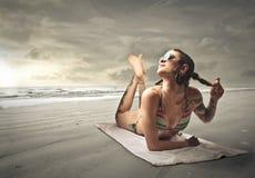 Tattoed girl. Sitting at the beach stock photo