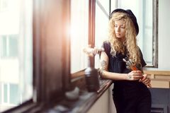 Curly Blonde Tattoed Artist with Brushes. Tattoed long hair female artist in nice black hat looking in window, she holding her brush royalty free stock photo