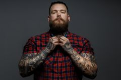 Tattoed men in red shirt. Tattoed man with beard, red shirt in a section,holds hands on a breast. Grey background stock photos