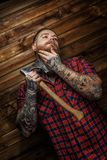 Tattoed man hang axe on wooden background. Tattoed man in red shirt in a section with beard hang axe on wooden backgroud. One hand near man face stock photos