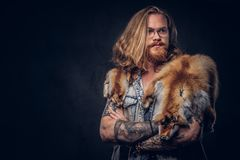 Tattoed redhead hipster male with long luxuriant hair and full beard dressed in a t-shirt and jacket holds the fox skin stock photo