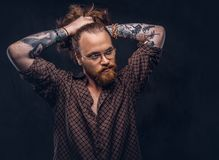 Tattoed redhead man hipster corrects his lush hair dressed in a brown shirt, standing at a studio. Isolated on a dark. Tattoed redhead man hipster corrects his stock photos
