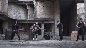 Rockers in gothic style and make-up playing metal rock with guitar and drum kit on the background of abandoned building. Tattoed rockers in gothic style and make stock video