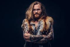Tattoed-Rothaarigehippie-Mann mit dem langen luxuriösen Haar und dem Vollbart, die in einem T-Shirt und in einer Jacke gekleidet  stockfotografie
