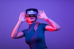 Tattoed sexig kvinna som bär en huvuduppsättning för virtuell verklighet VR Royaltyfri Foto