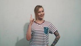 Tattoed vrij blondemeisje in gestreept overhemd, hebben idee en trekken vinger uit stock video
