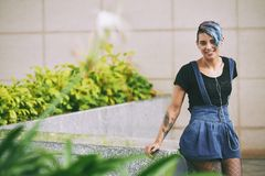 Tattoed woman. Tattoed attractive smiling young woman standing outdoors stock images