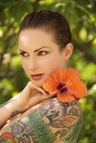 Tattoed woman with flowers. Attractive Caucasian tattooed woman with Hibiscus flower over her shoulder in Maui, Hawaii, USA Stock Photos