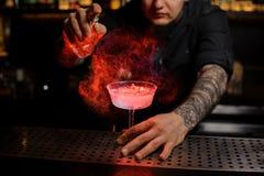 Tattoedbarman het bespuiten op de heerlijke cocktail van de verstuiver stock foto