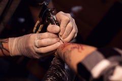 Tattoer using tattoo machine Royalty Free Stock Images