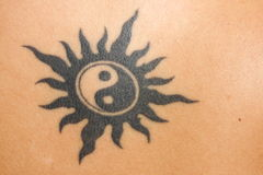 Tattoo. Jing Jang symbol on skin background royalty free stock image