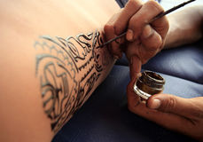 Tattoo. Artist draws a tattoo henna on a male body royalty free stock photo