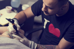 Tattoo art. Male tattoo artist holding a tattoo gun, showing a process of making tattoos on a male tattooed model's arm royalty free stock photography