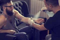 Tattoo art. Male tattoo artist holding a tattoo gun, showing a process of making tattoos on a male tattooed model's arm stock image