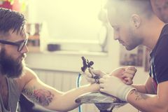 Tattoo art. Male tattoo artist holding a tattoo gun, showing a process of making tattoos on a male tattooed model's arm stock images