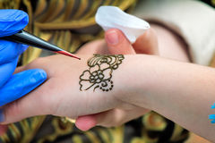 A tattoo artist applying his craft onto the hand of a female. Tool for tattoos tattoo artist make a drawing on the back of the hand of the girl stock photography